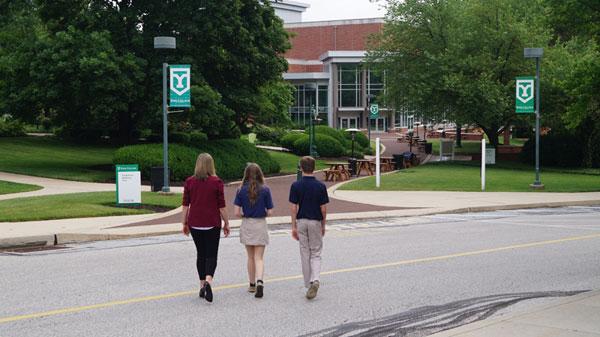 3 people walking across college campus