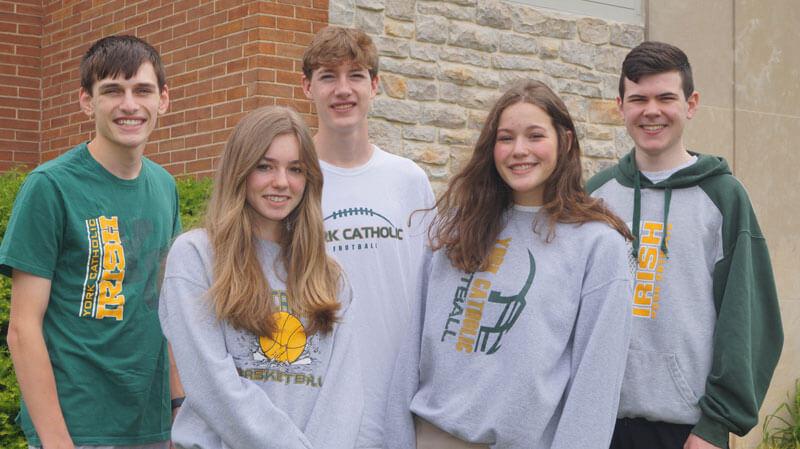 5 smiling students wearing spirit wear