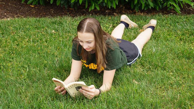 summer reading lying in grass